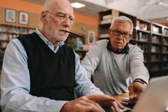 Senior men sitting in a classroom working on laptop. Two elderly men sitting in classroom and working together on a laptop computer. Senior men sitting in a royalty free stock photos
