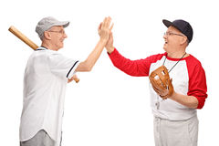 Senior men in sportswear high-five each other. Studio shot of two senior men in baseball outfits high-five each other isolated on white background stock images