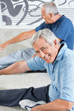 Senior men stretching in fitness. Center before exercising stock photography