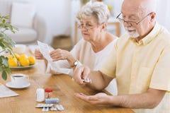 Senior man taking medication. Senior men taking medication for diabetes while his wife reading a prescription Stock Photos