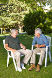 Senior men talking in a garden Royalty Free Stock Photos