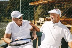 Two senior men sitting near a tennis court and talking. Senior men talking to each other sitting on bench during a game of tennis. Cheerful senior men in tennis stock photo