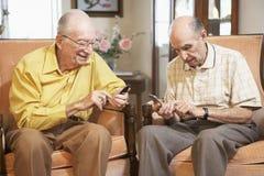Senior men text messaging. Two Senior men text messaging Stock Photography