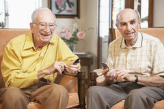Senior men text messaging. Two Senior men text messaging Stock Images