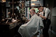 Senior man visiting hairstylist in barber shop. Stock Images