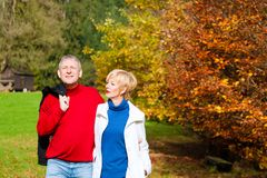 Matured man and woman in park for walk stock photo