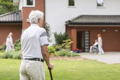 Senior man with walking stick during stay in a nursing house. Bl. Senior men with walking stick during stay in a nursing house. Blurred background stock images