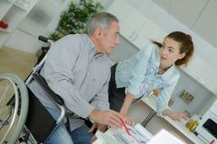 Senior man in wheelchair with extended care assistant royalty free stock image