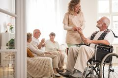 Senior man on wheelchair with helpful nurse holding his hand and friends sitting on couch drinking tea stock photography