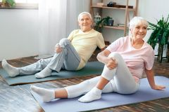 Senior couple doing yoga together at home health care leg stretching