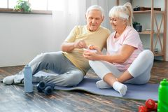 Senior couple exercise together at home health care healthy nutrition. Senior men and women exercise together indoors eating carrot healthy snack smiling Royalty Free Stock Photo
