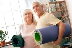 Senior couple exercise together at home health care holding yoga mats looking camera. Senior men and women exercise together indoors stading hugging holding yoga Stock Photo