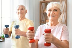 Senior couple exercise together at home health care with dumbbells looking camera. Senior men and women exercise together indoors standing holding dumbbells in stock photos