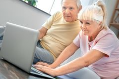 Senior couple exercise together at home health care watching training video. Senior men and women exercise together indoors watching training tutorial on a Royalty Free Stock Photo
