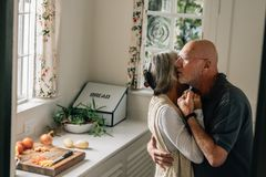 Senior man and woman expressing their love for each other with a warm hug. Elderly couple embracing each other standing in kitchen royalty free stock image
