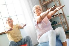 Senior couple exercise together at home doing aerobics hands in front. Senior men and women together indoors sitting on exercise ball doing aerobics hands in royalty free stock images