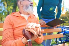 Senior man with young caregiver. Senior men with young caregiver in park royalty free stock photo