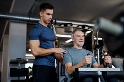 A senior man with a young trainer doing strength workout exercise in gym. stock images