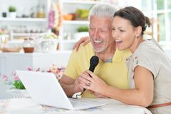 Senior man with young woman singing karaoke. Senior men with young women singing karaoke with laptop at home Stock Photos