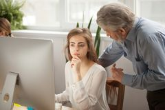 Senior mentor teaching young female intern using computer in off. Senior mentor teaching female intern using computer in office, old executive training young Stock Image