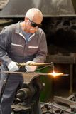 Senior metalworker using gas torch. Man Stock Images