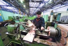 Senior milling machine operator works at machine Stock Photos