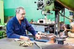 Senior milling machine operator works at machine Stock Photography