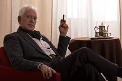 Senior millionaire smoking cigar Stock Images