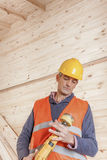 Senior minority construction worker on the job site. Older man inspecting a electric drill Royalty Free Stock Photos