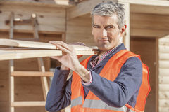 Senior minority construction worker on the job site. Older construction working carrying wood Royalty Free Stock Photos