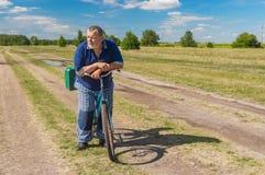 Senior mit dem grünen Koffer, der fertig wird, auf ein Fahrrad zu fahren Lizenzfreies Stockfoto