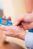 Senior mit Diabetes unter Verwendung des Blutzuckeranalysators Stockfoto
