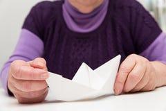 Senior mit einem Papierboot Stockfotografie