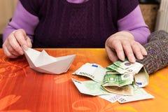 Senior mit einer Socke voll vom Geld Stockfotografie