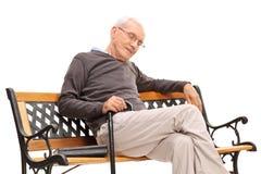 Senior mit Stock schlafend auf einer Holzbank Stockfotografie