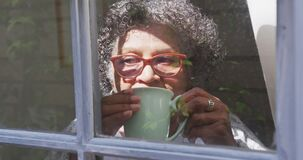 Senior mixed race woman enjoying drinking tea. Social distancing and self isolation in quarantine