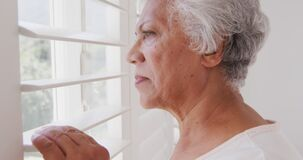 Senior African American woman looking at her window, at home