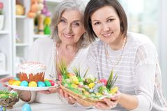 Close-up portrait of mother and daughter colouring eggs. Senior mother and adult daughter colouring eggs to Easter royalty free stock image