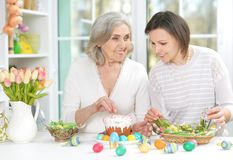 Portrait of mother and daughter colouring eggs. Senior mother and adult daughter colouring eggs to Easter royalty free stock photo