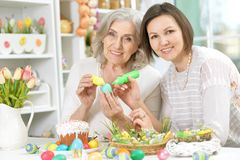 Portrait of mother and daughter colouring eggs. Senior mother and adult daughter colouring eggs to Easter royalty free stock photos