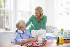 Senior Mother And Adult Daughter Use Sewing Machine At Home Royalty Free Stock Photography