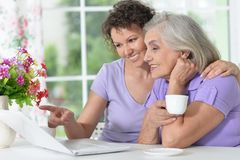 Senior mother and adult daughter working with laptop Stock Photo