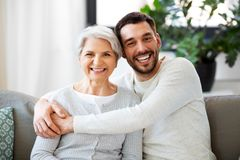 Senior mother with adult son hugging at home stock photos