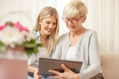 Senior mother and daughter smiling and looking at the tablet. Flower bouquet in foreground. royalty free stock photography