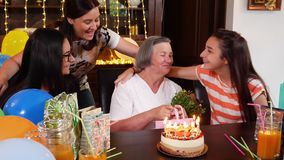 Senior mother with daughter and granddaughters at birthday party stock footage