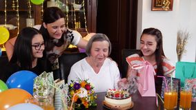 Senior mother with daughter and granddaughters blowing candles on birthday cake stock footage