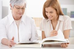 Senior mother and daughter looking at photo album Stock Images