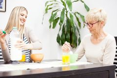 Senior mother and her daughter talking and eating healthy cereal breakfast royalty free stock photos