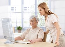 Senior mother and daughter using computer stock photography