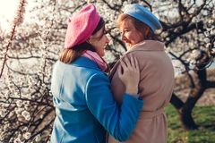 Senior mother and her adult daughter hugging in blooming garden. Mother`s day concept. Family values stock photography